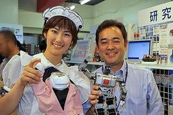 ロボットを手に持つテクノロジア株式会社 荒井貞博氏(右)と、アキバガイドのメイドさん(左)