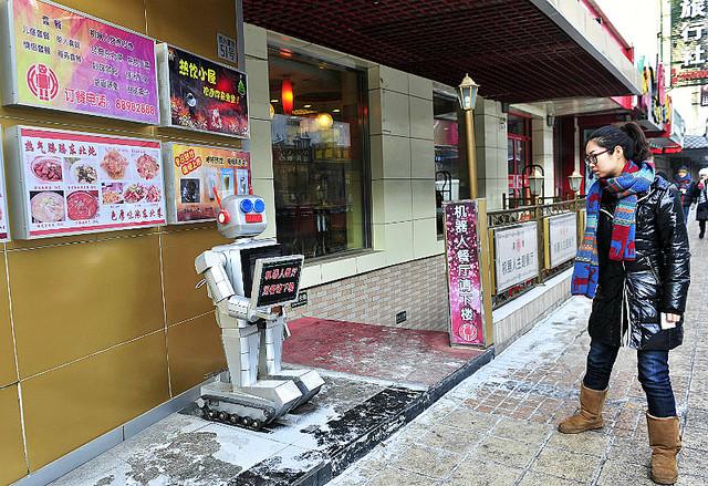 店の外でお客を出迎える専門のロボットと、それに見入る歩行者