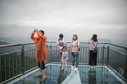 中国・重慶の峡谷の上に架けられた世界最長の片持ちばりのガラスの展望橋の上で写真を撮る観光客ら(2017年6月1日撮影)。(c)AFP=時事/AFPBB News