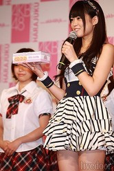 オススメ商品として、「ロールケーキ」を手にするAKB48の前田亜美