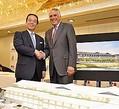 8日、京都の平安神宮会館で正式契約を締結し、固く握手を交わす積水ハウスの和田会長とマリオット・インターナショナルのサイモンFクーパー。「ザ・リッツ・カールトン京都」は2014年春の開業を目指す