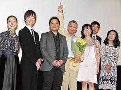花束を手に笑顔を見せる橋口亮輔監督