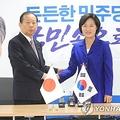 二階氏(左)と握手を交わす秋氏=12日、ソウル(聯合ニュース)