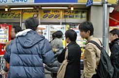 「おでん缶」を買おうとチチブデンキ店頭の自販機前に並ぶ人の列。(撮影:関口哲司)