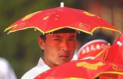 猛暑が続いている北京で人気なのが、頭にかぶる「国旗日傘」だ。写真は、故宮博物院で売られたもの。見学客が買い求めていた。