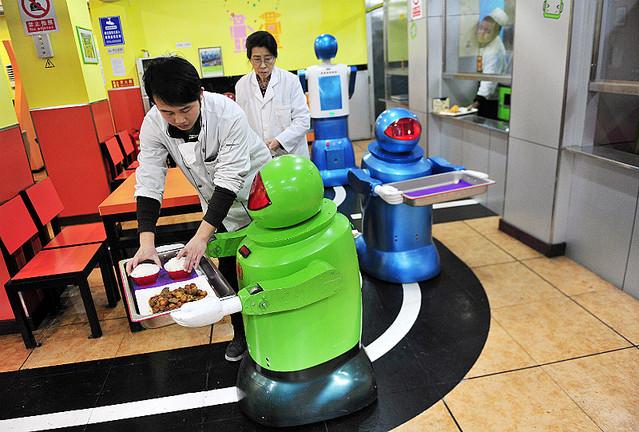 配膳専門ロボットのトレーの上に、料理を載せる人間の店員
