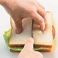ナイフの両脇のパンを手で押さえて切る