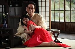 金魚の正体を思わせる赤い衣装に身を包んだ二階堂ふみと、老作家役の大杉漣