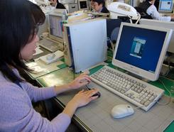 「生体認証システム」で指をセンサーにあてる職員。(写真提供:東京都北区)