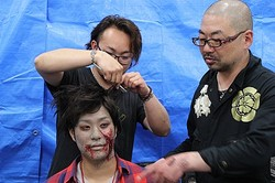 ゾンビメイクを指導する特殊造型アーティストの西村喜廣(左)