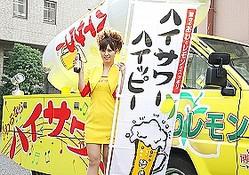 ハイサワー号を前に微笑むハイサワーガールの上條彩佳さん。手に持つのは「ハイサワー ハイッピーゼロ ビアテイスト」