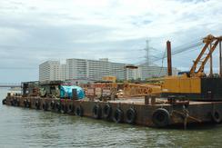 14日、大停電の原因となった東電の高圧送電線を破損した三国屋(みくにや)建設所有のクレーン船。対岸は東京都。画面左が東京湾。(撮影:佐藤学)