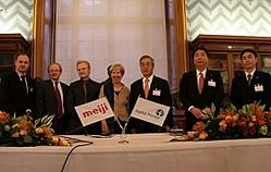 調印式でカメラに収まる明治・馬場良雄取締役常務執行役員(右から3人目)、その左がアリス・ドートリ所長