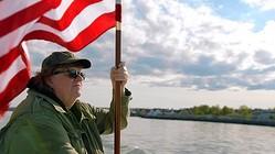 ムーア監督が星条旗を手に! - 映画『マイケル・ムーアの世界侵略のススメ』  - (C)2015, NORTH END PRODUCTIONS
