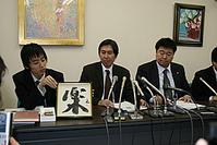 記者会見で、「楽」と書いた額などを示す弁護団