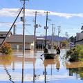 冠水した道路をボートで救助に向かう陸上自衛隊員=13日午前、宮城県丸森町