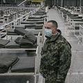 セルビア・ベオグラードのイベント会場で、新型コロナウイルス感染症の軽度の患者を収容するために並べられたベッドの間に立つ兵士(2020年3月24日撮影)。(c)Vladimir Zivojinovic / AFP