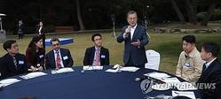 青瓦台担当記者ら招いて行われた行事であいさつする文大統領(右から3人目)=25日、ソウル(聯合ニュース)
