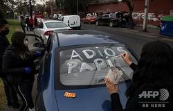 チリ・サンティアゴの病院の遺体安置所前で、父親のひつぎを乗せた車の後部窓に「さようなら、パパ」と書く女性(2020年6月22日撮影)。(c)MARTIN BERNETTI / AFP