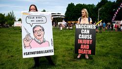 2020年5月9日、ワシントン州オリンピアの州会議事堂前で行われたジェイ・インスレー知事の自宅待機命令に反対するデモで、反ワクチンを主張するプラカードを持つ2人の女性 (Photo by JASON REDMOND/AFP/Getty Images)