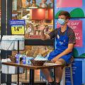米小売り大手クローガーの店舗前で手を挙げる男性(同社提供)