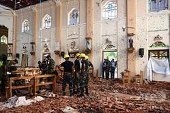 スリランカで起きた連続爆発事件の現場の一つ、ネゴンボの聖セバスチャン教会で現場検証を行う治安部隊(2019年4月22日撮影)。(c)Jewel SAMAD / AFP