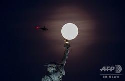 米ニューヨークで観測された、自由の女神像の上に輝く満月(2019年5月18日撮影、資料写真)。(c)Johannes EISELE / AFP
