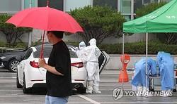 光州市内の駐車場に設けられたドライブスルー型専用診療所で雨の中、検体を採取する医療関係者=6日、光州(聯合ニュース)