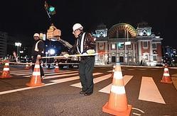 中之島通の一部を歩行者空間にするための工事。車両の進入を防ぐコーンなどを設置する作業員=15日午後8時26分、大阪市北区(安元雄太撮影)