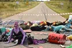 豪クイーンズランド州ボーエン近くのアボットポイント港へ通じる路上で、インド資本のアダニ・グループによる炭鉱開発に抗議する環境活動家たち(2019年5月1日撮影)。(c)PETER PARKS / AFP
