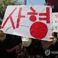 地裁前で死刑求刑を求める市民=14日、ソウル(聯合ニュース)