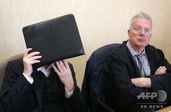 独ケルンの裁判所で、画家ゲルハルト・リヒター氏が捨てた作品を拾って売ろうとしたとして、窃盗罪で罰金刑を言い渡され顔を隠す被告(左)と被告側弁護人(2019年4月24日撮影)。(c)Oliver Berg / dpa / AFP