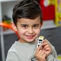 大好きなパトカーのおもちゃを見せる男の子(画像は『The Sun 2021年5月5日付「999 TOY HERO Boy, 4, with speech difficulties read the number on his toy car to call 999 after his mum had a seizure」(Credit: News Group Newspapers Ltd)』のスクリーンショット)