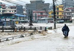 ネパールの首都カトマンズで、冠水した道路を歩く人(2019年7月12日撮影)。(c)PRAKASH MATHEMA / AFP
