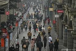 中国中部・湖北省武漢の通りを歩く人々(2021年1月23日撮影)。(c)Hector RETAMAL / AFP