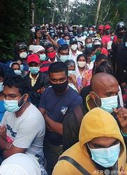 新型コロナウイルス「治療薬」のサンプルを求め、スリランカ中部の村に集まった人々(2020年12月8日撮影)。(c)AFP