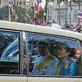 タイの首都バンコクで、民主派抗議デモ参加者らが沿道で3本指を立てる中、車で通過するスティダー王妃(中央)とティパンコーン・ラッサミチョト王子(2020年10月14日撮影)。(c)Teera NOISAKRAN / AFP