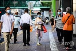 マスクを着けた歩行者ら。香港にて(2020年7月29日撮影)。(c)ANTHONY WALLACE / AFP