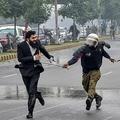 パキスタン東部ラホールで、弁護士を追う警察官(2019年12月11日撮影)。(c)ARIF ALI / AFP