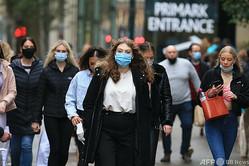 英イングランド北部のウェストヨークシャー州リーズで、マスクをして市内を歩く市民ら(2020年10月30日撮影)。(c)Lindsey Parnaby / AFP