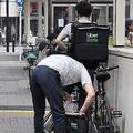 池袋駅周辺で待機するウーバーイーツの配達員ら。各地で似たような待機する配達員の姿が見られる(時事通信フォト)