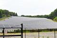 牧草地の傾斜を利用して稼働中の太陽光発電施設=2019年6月27日午前10時49分、福島県大玉村、深津弘撮影
