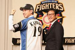 日本ハムのユニホームに袖を通した金子弌大(左)と栗山監督【写真:石川加奈子】
