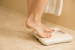 Close up of a caucasian woman with red painted toenails stepping on a bathroom weight scale.  She is excited to read the scale, which shows that she has lost weight. Beige tiled floor and walls. White towel.  Dieting, weight loss concept.  Unrecognizable person.