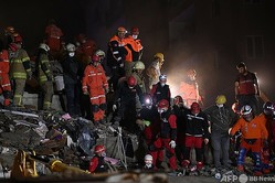 トルコ・イズミルで、倒壊した建物のがれきから生存者を捜索する救助隊員ら(2020年10月31日撮影)。(c)OZAN KOSE / AFP