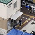 警察官が刺され拳銃が奪われた千里山交番(左)周辺を調べる捜査員=16日、大阪府吹田市(提供・共同通信社)