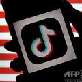 動画共有アプリ「ティックトック」のロゴと米国旗(2020年8月3日撮影、資料写真)。(c)Olivier DOULIERY / AFP