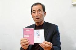 来日時に携えていた旅券と被爆者健康手帳を手に、入国審査の状況を説明する韓国原爆被害者協会の沈鎮泰・陜川支部長=韓国・慶尚南道陜川郡、武田肇撮影