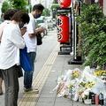 稲田真優子さんが殺害されたビルの前には花束や飲み物が供えられ、手を合わせる人が絶えなかった=20日午後、大阪市北区(永田直也撮影)