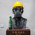 香港の大学に設置された銅像に置かれた黄色いヘルメット、ガスマスク、火炎瓶(2019年11月13日撮影、資料写真)。(c)ANTHONY WALLACE / AFP